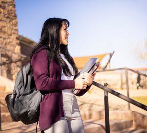 A Hispanic woman walks down stairs outside.