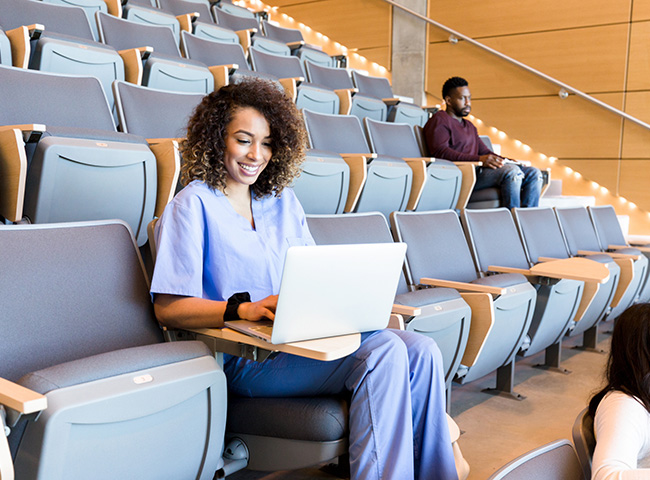 A grad student studying nursing works at her laptop in a lecture hall.