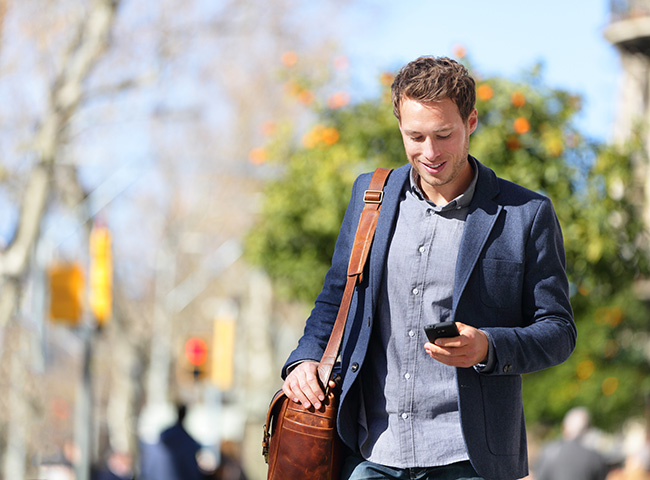 A recent grad walks outside with his phone to help with his job search.