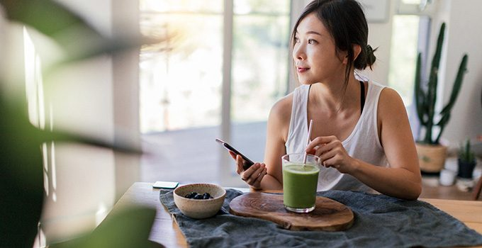 A freelancer sits in her home with a green smoothie.